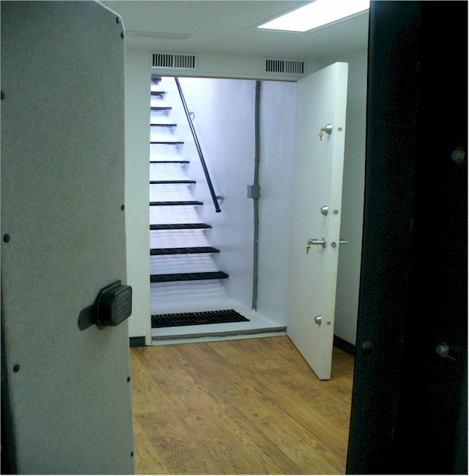 open safe room door with stairwell  leading up  to  house